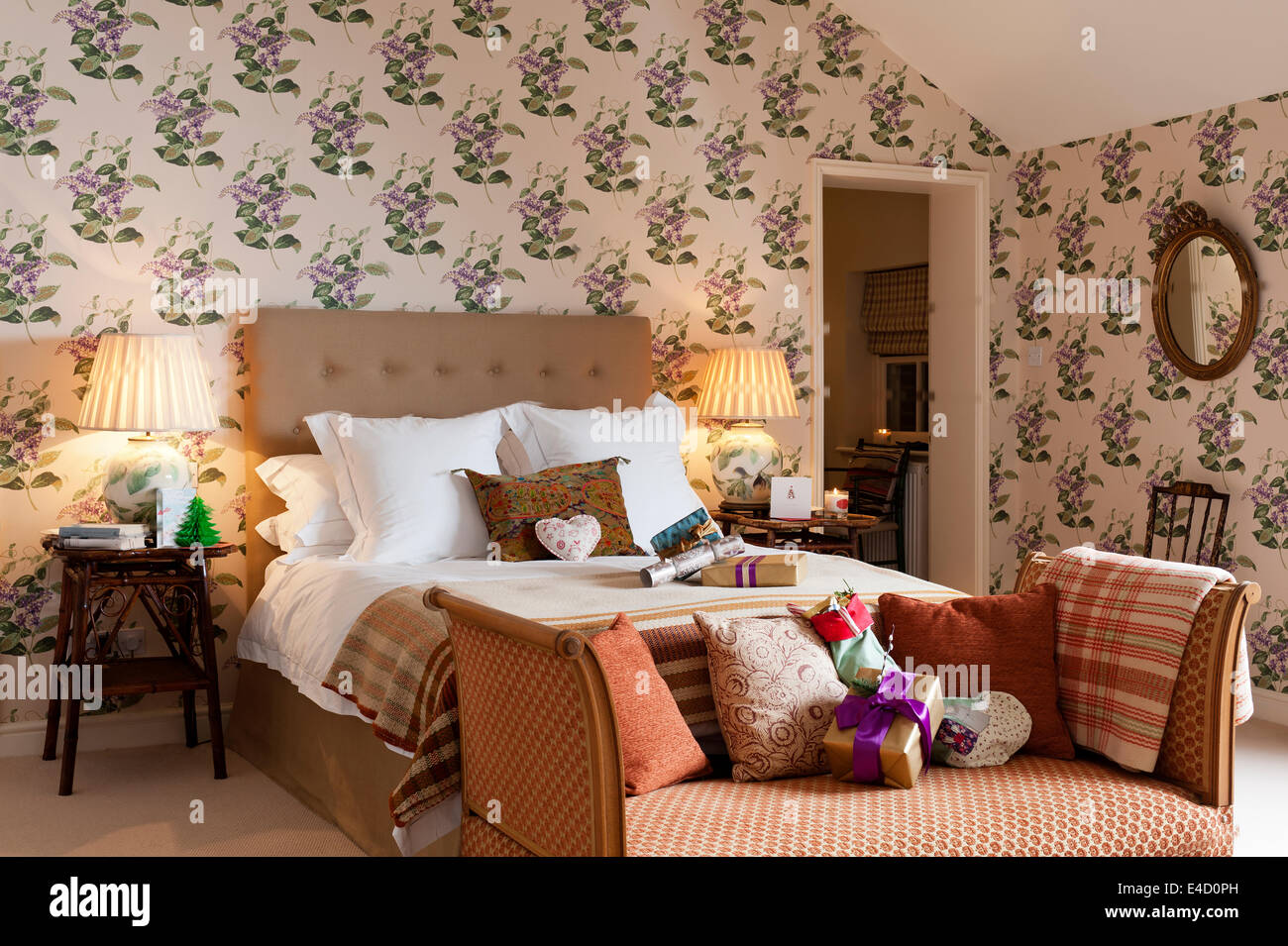An Edwardian day bed in original upholstery sits at the end of a bed in a bedroom with floral patterned wallpaper - Stock Image