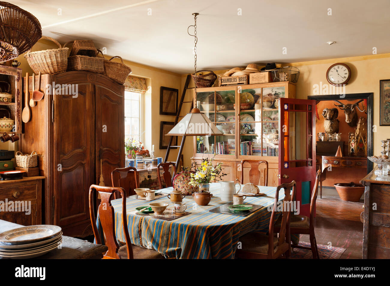 Charming Country Kitchen Stuffed With Antiques. Wicker Baskets Are Piled On  Top Of A Large Armoire And Tea And Bread Are Laid On