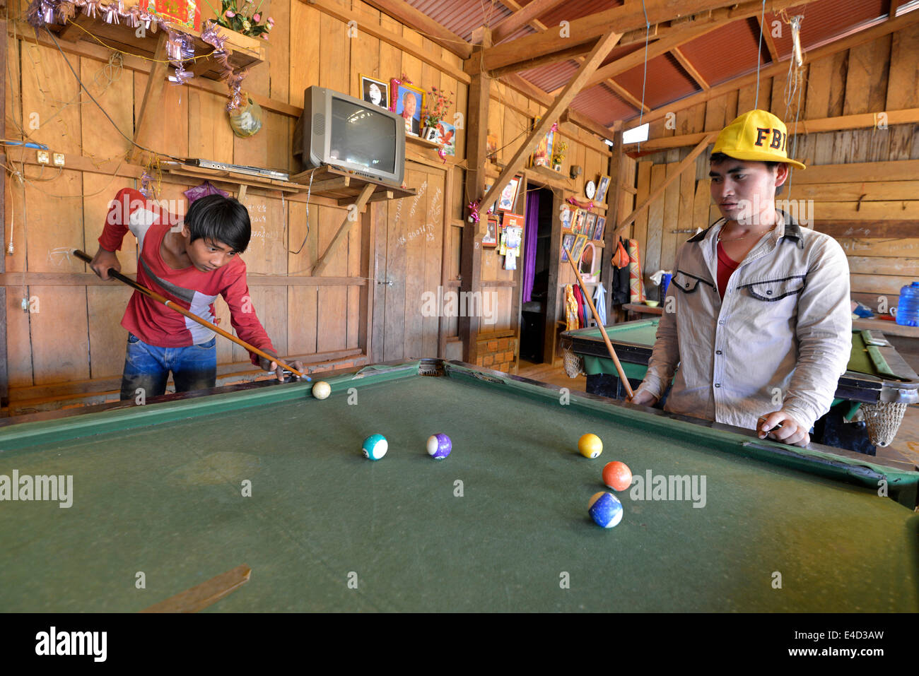 Two Cambodian youths playing pool billiards in a simple wooden hut, Banlung, Ratanakiri Province, Cambodia - Stock Image
