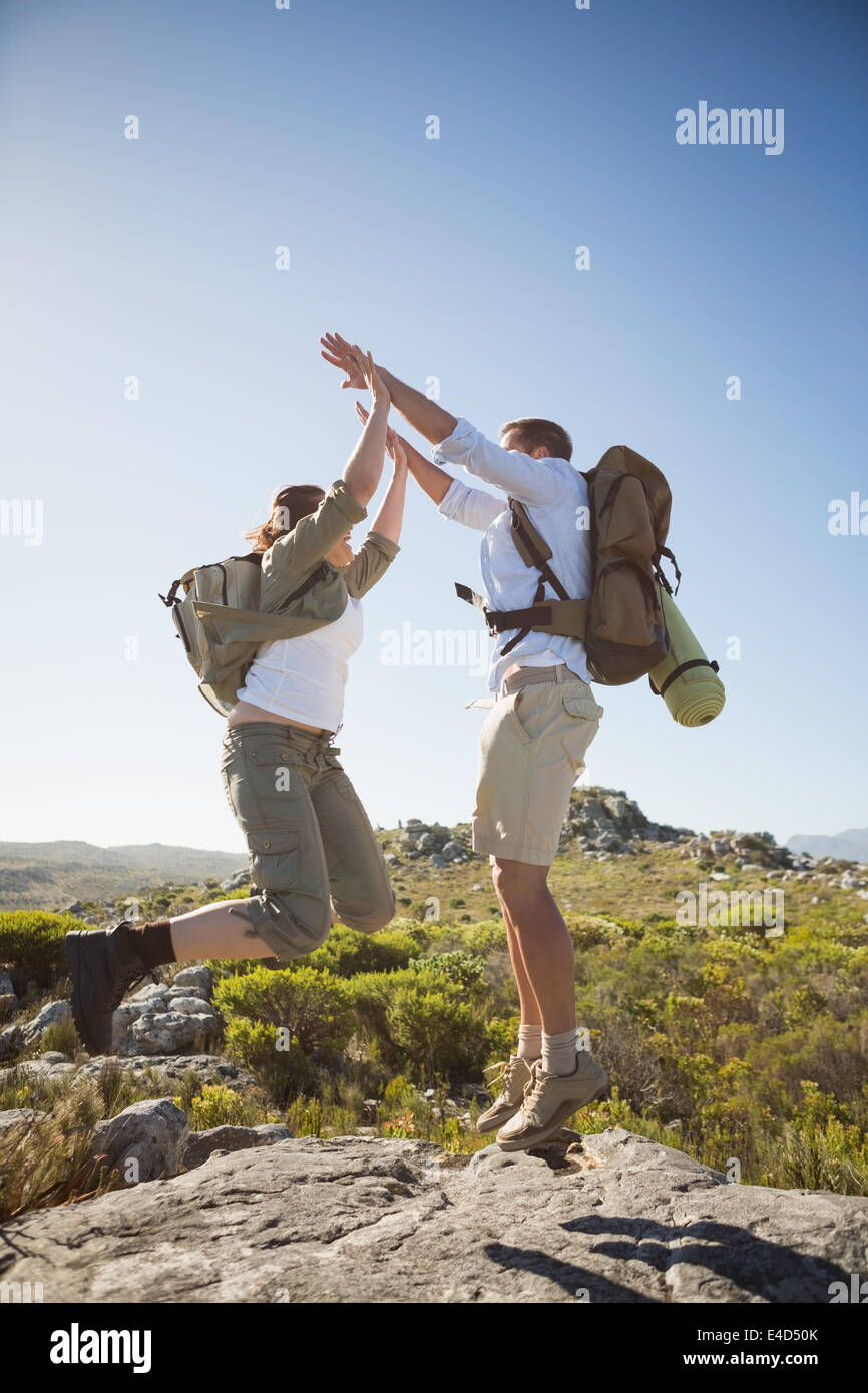 Hiking couple jumping and cheering on rocky terrain - Stock Image