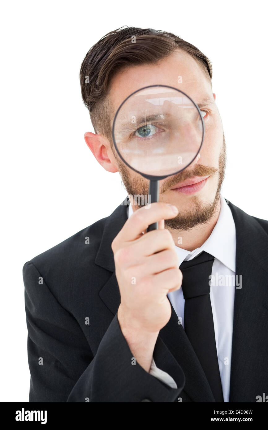 Geeky businessman looking through magnifying glass - Stock Image