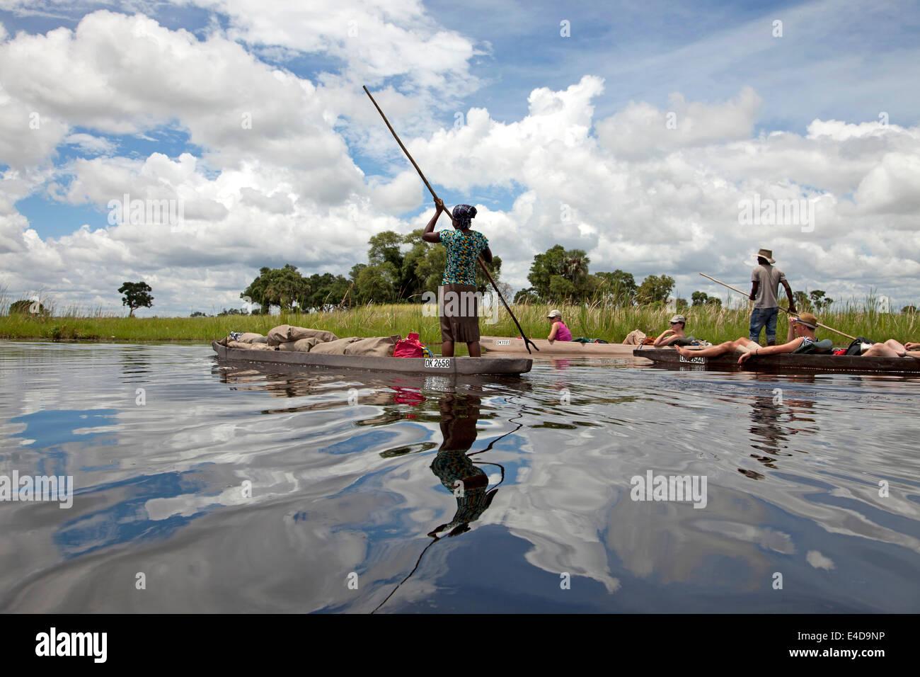 tourists  on a traditional mokoro boat in the Okavango Delta, Botswana, Africa - Stock Image