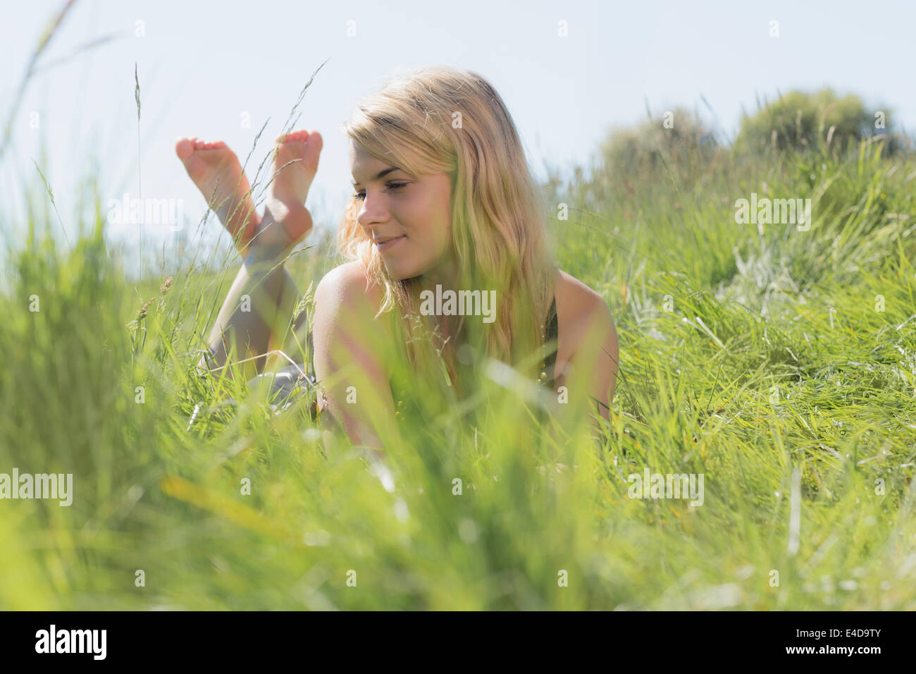 Pretty blonde in sundress lying on grass - Stock Image