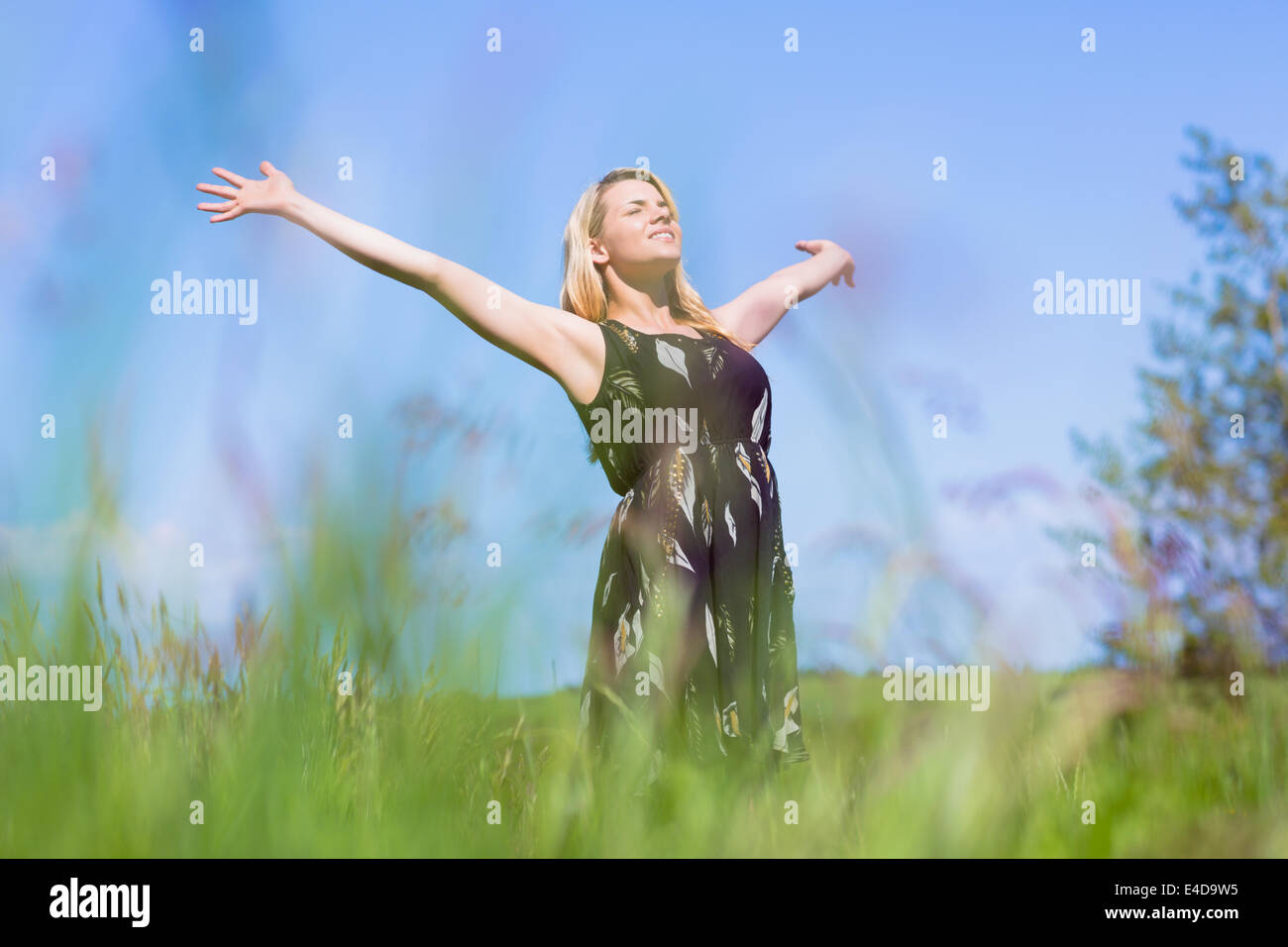 Pretty blonde in sundress standing with arms out - Stock Image