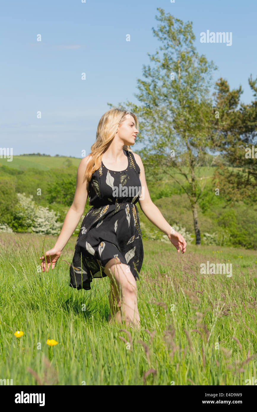 Pretty blonde in sundress walking through field - Stock Image
