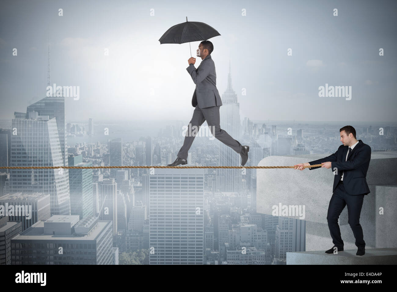 Young business man pulling a tightrope for businessman Stock Photo