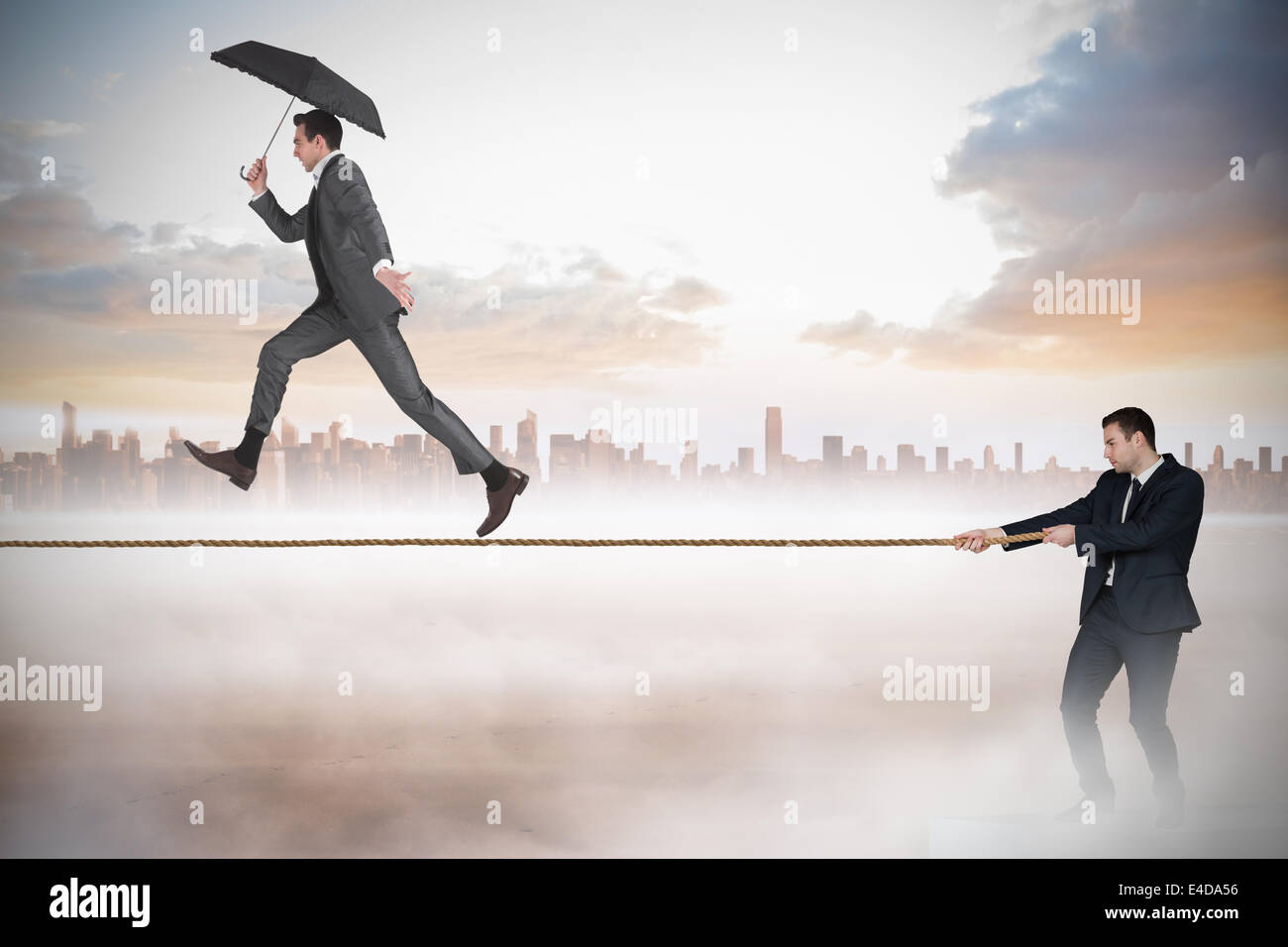 Young businessman pulling a tightrope for business man - Stock Image