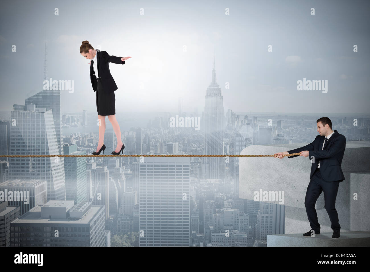 Young businessman pulling a tightrope for business woman - Stock Image