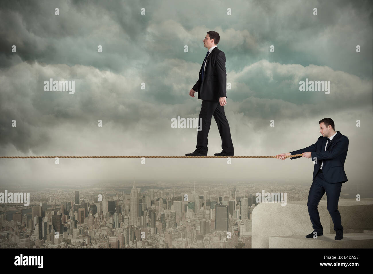 Young business man pulling a tightrope for businessman - Stock Image