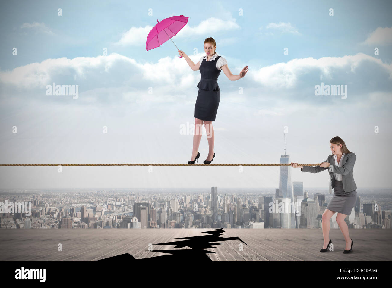 Young business woman pulling a tightrope for businesswoman - Stock Image