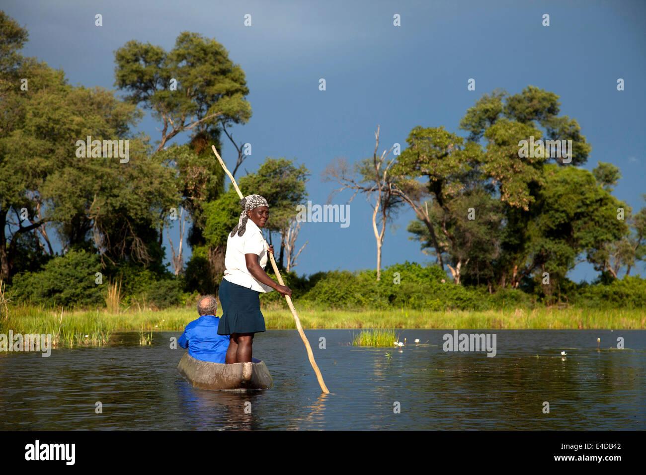 Bootsführer mit typischer Stake oder Stange und Touristen auf einem traditionellem Mokoro Boot im Okavango - Stock Image