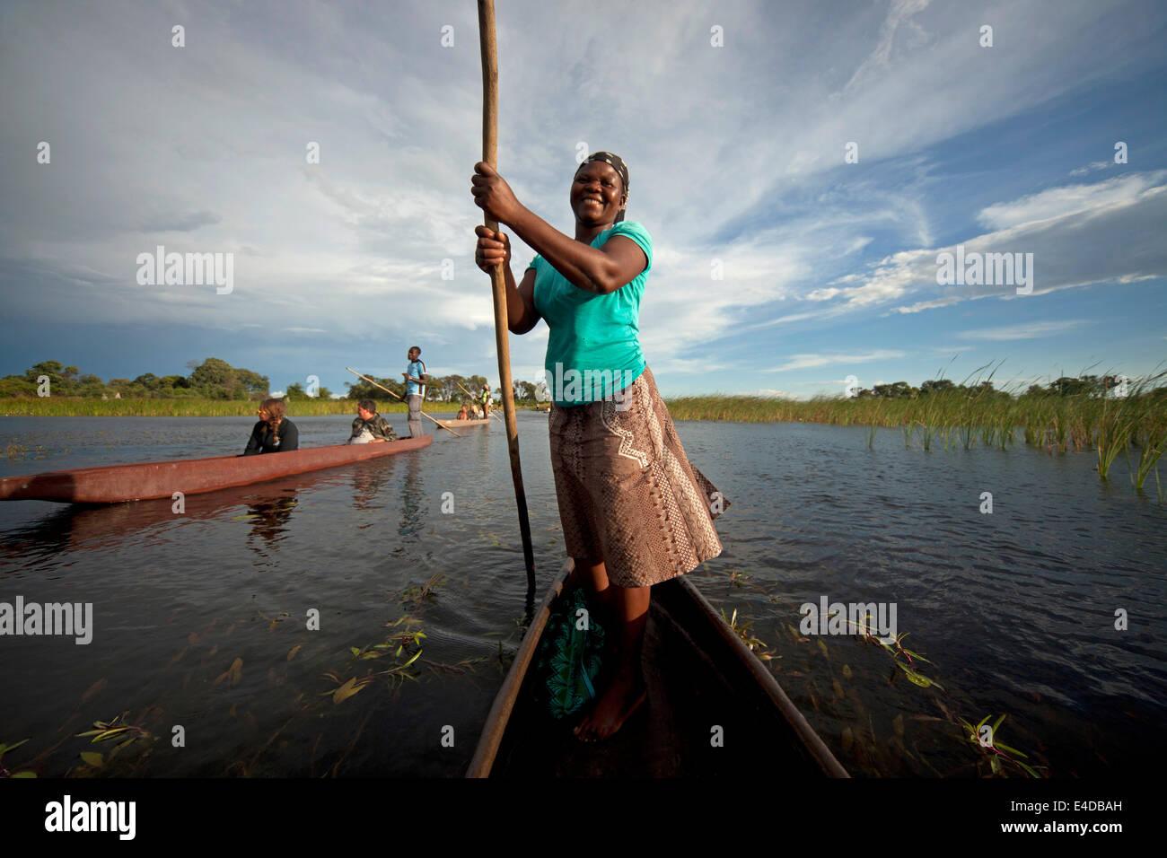Frau mit typischer Stake oder Stange auf einem traditionellem Mokoro Boot und Touristen im Okavango Delta, Botswana, - Stock Image