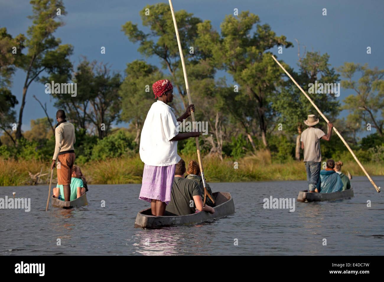Bootsführer mit typischer Stake oder Stange und Touristen auf einem traditionellem Mokoro Boot im Okavango Delta, Stock Photo