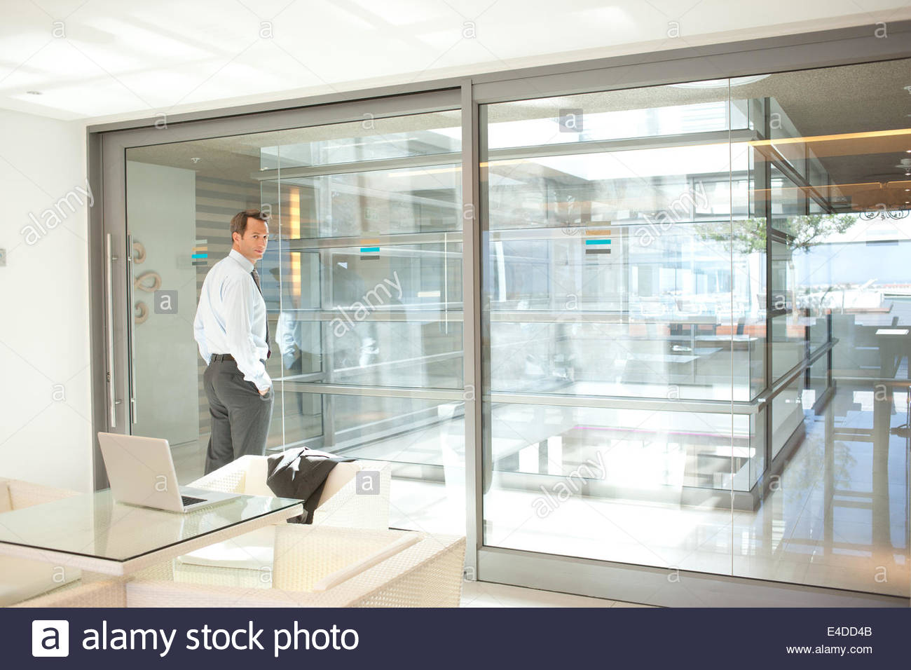 Businessman standing by glass wall in office - Stock Image