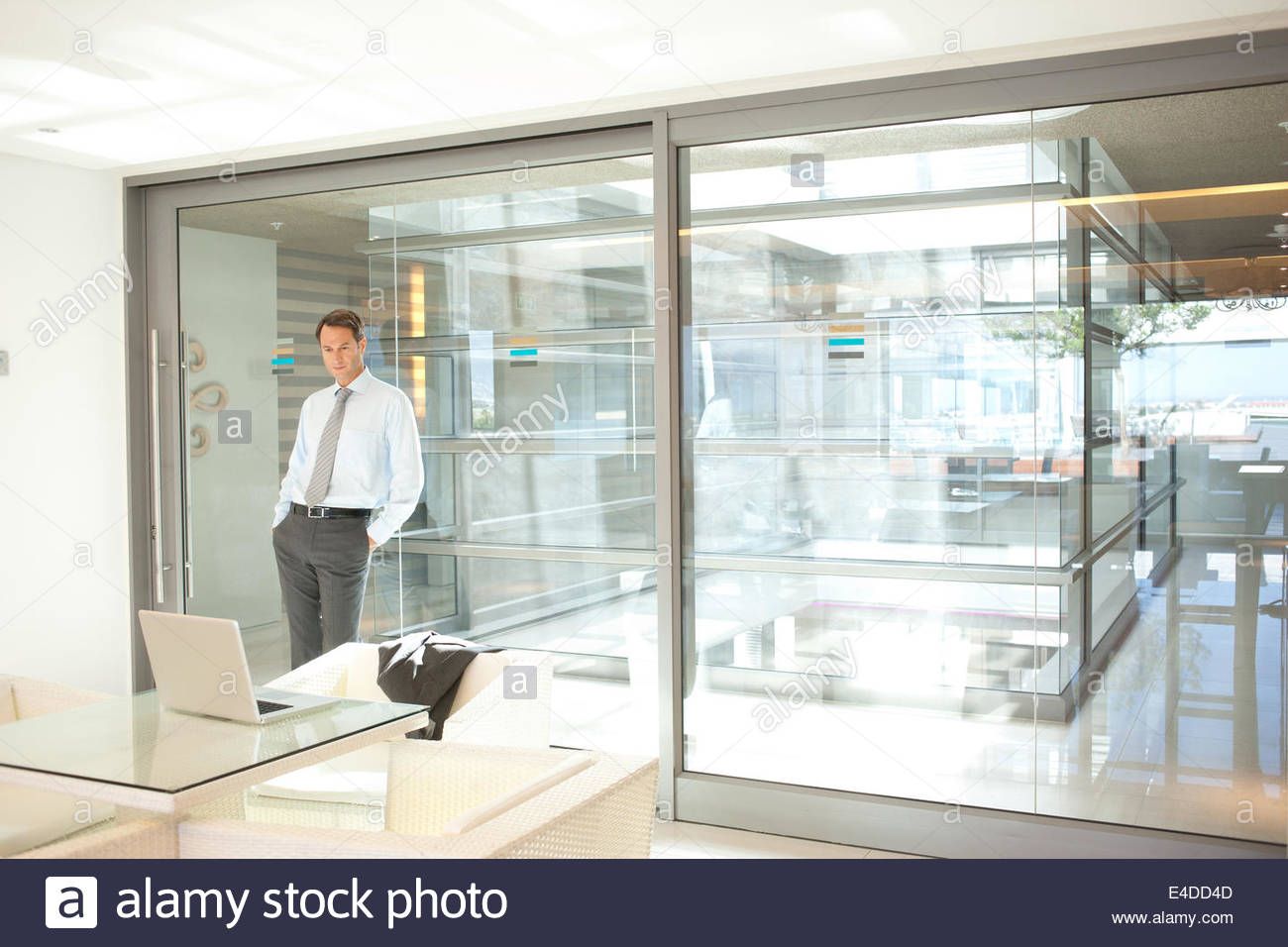 Businessman leaning against glass wall in office - Stock Image