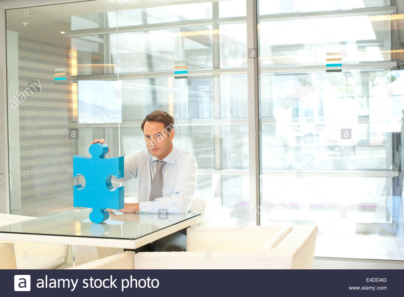 Businessman sitting at desk with jigsaw puzzle piece - Stock Image