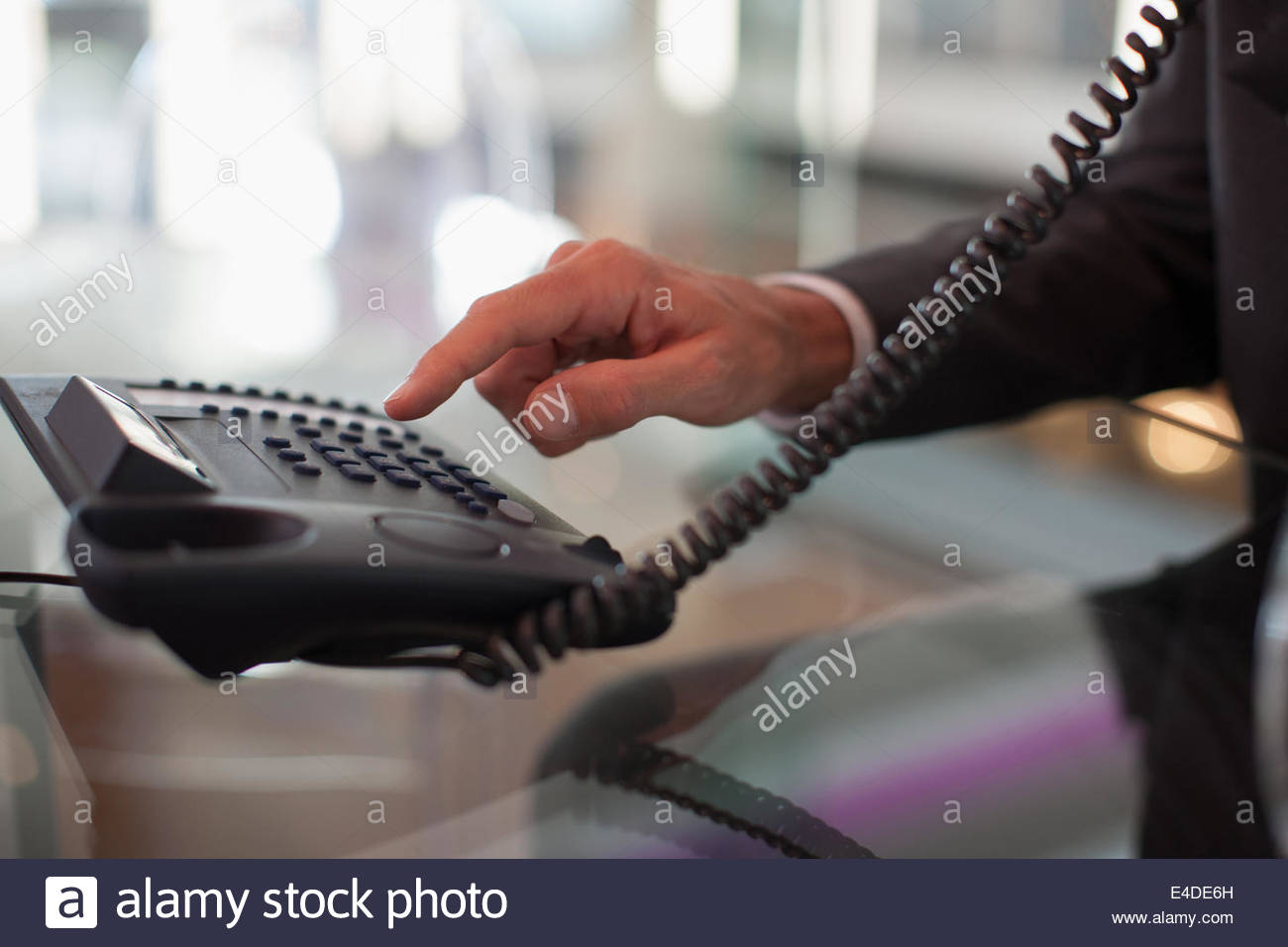 Businessman dialing telephone in office - Stock Image