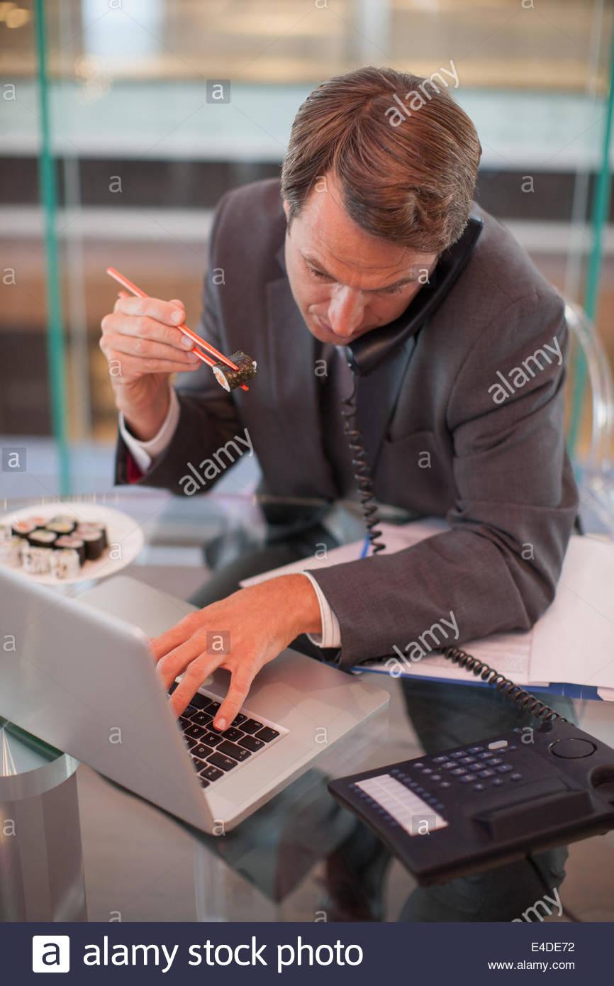 Businessman eating sushi and talking on telephone - Stock Image