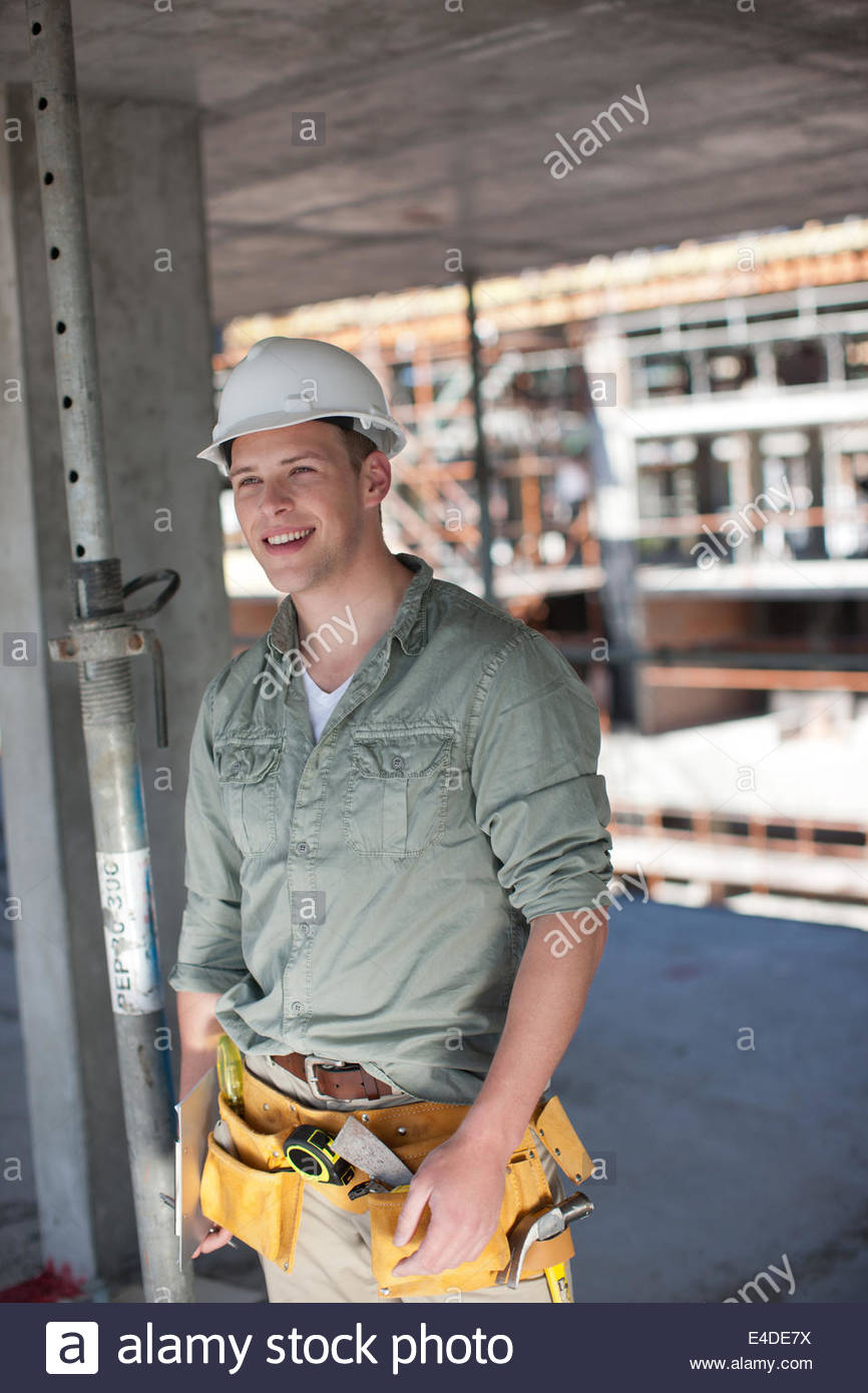 Construction worker smiling on construction site - Stock Image