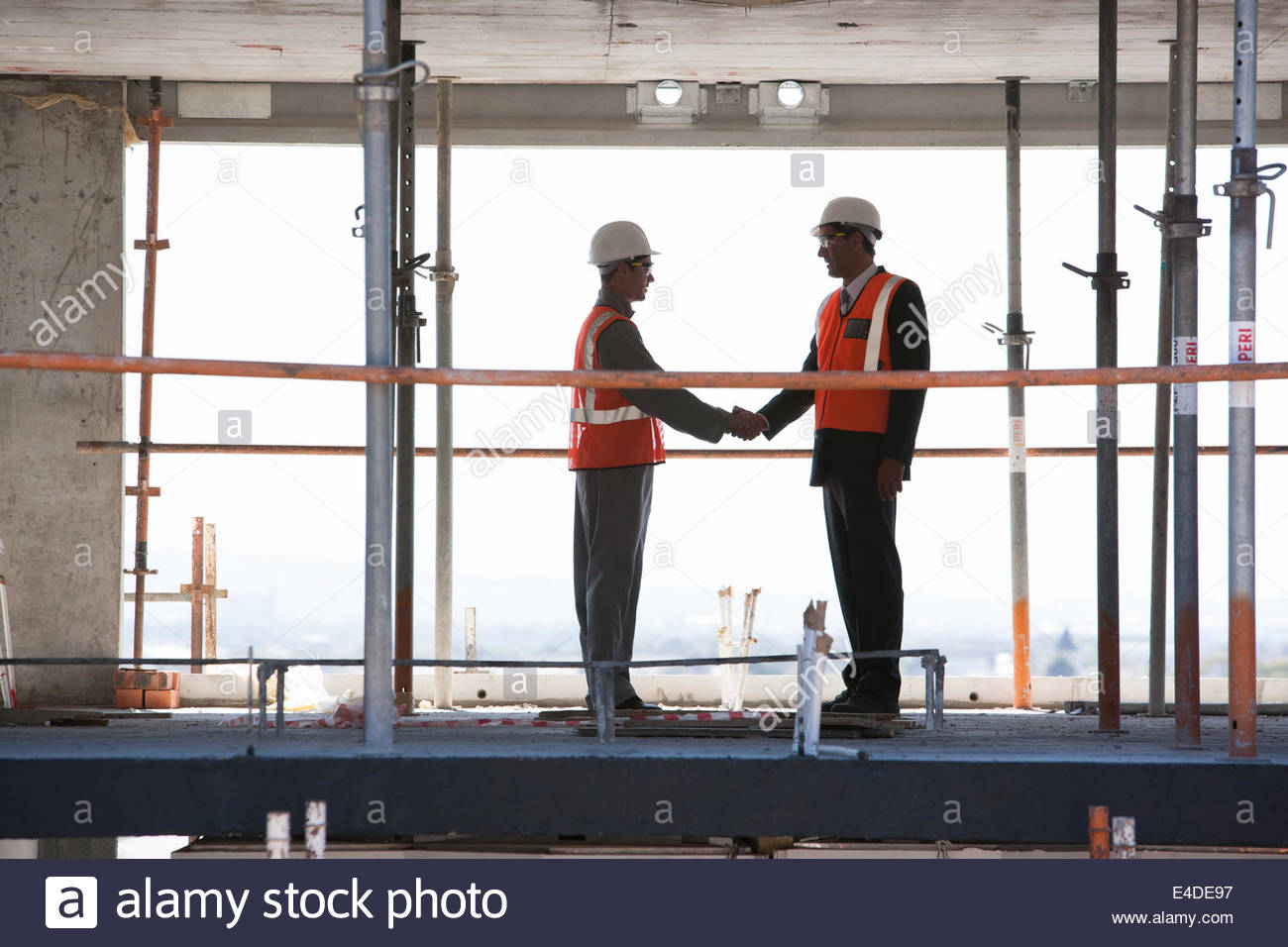 Construction workers shaking hands on construction site - Stock Image