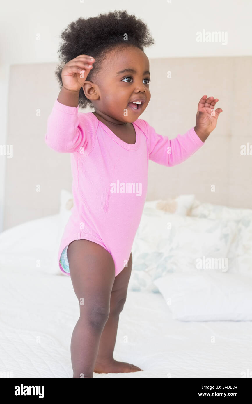Baby girl in pink babygro standing on bed - Stock Image