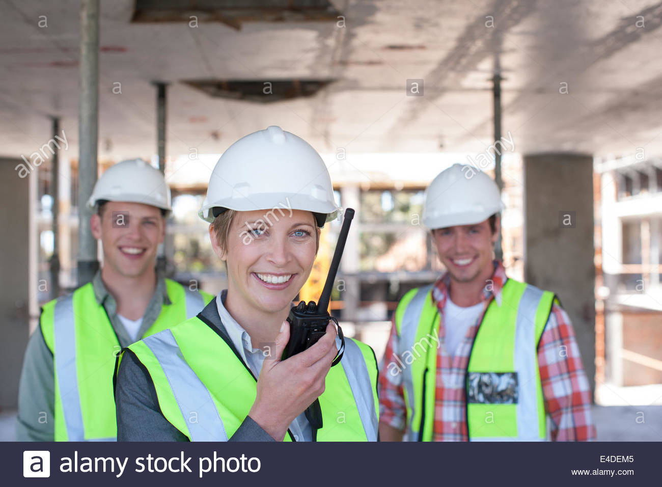 Construction worker holding walkie talkie on construction site - Stock Image