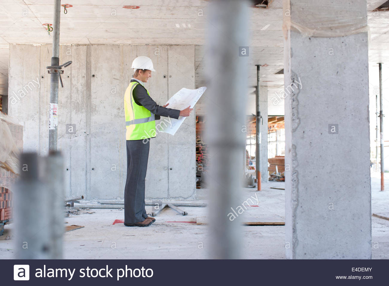 Construction worker holding blueprint on construction site - Stock Image