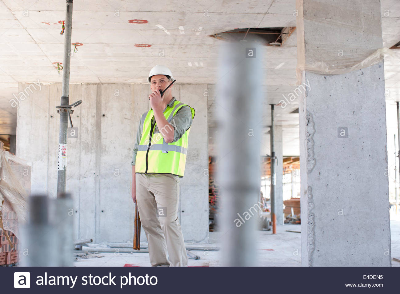 Construction worker talking on walkie talkie on construction site - Stock Image