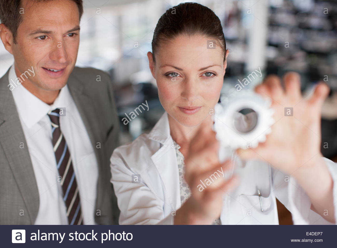Business people looking at cog - Stock Image