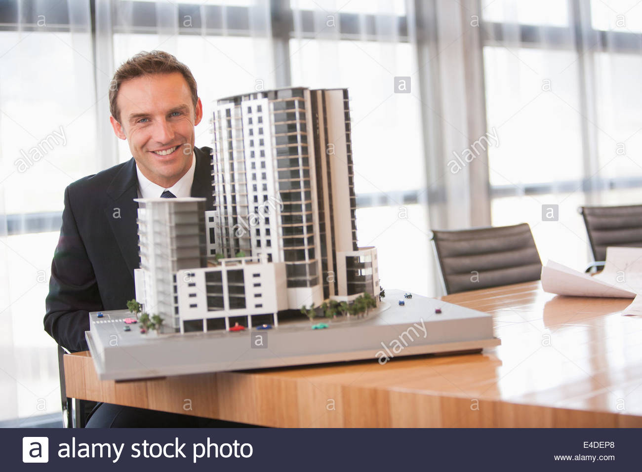 Businessman  in conference room with model building - Stock Image