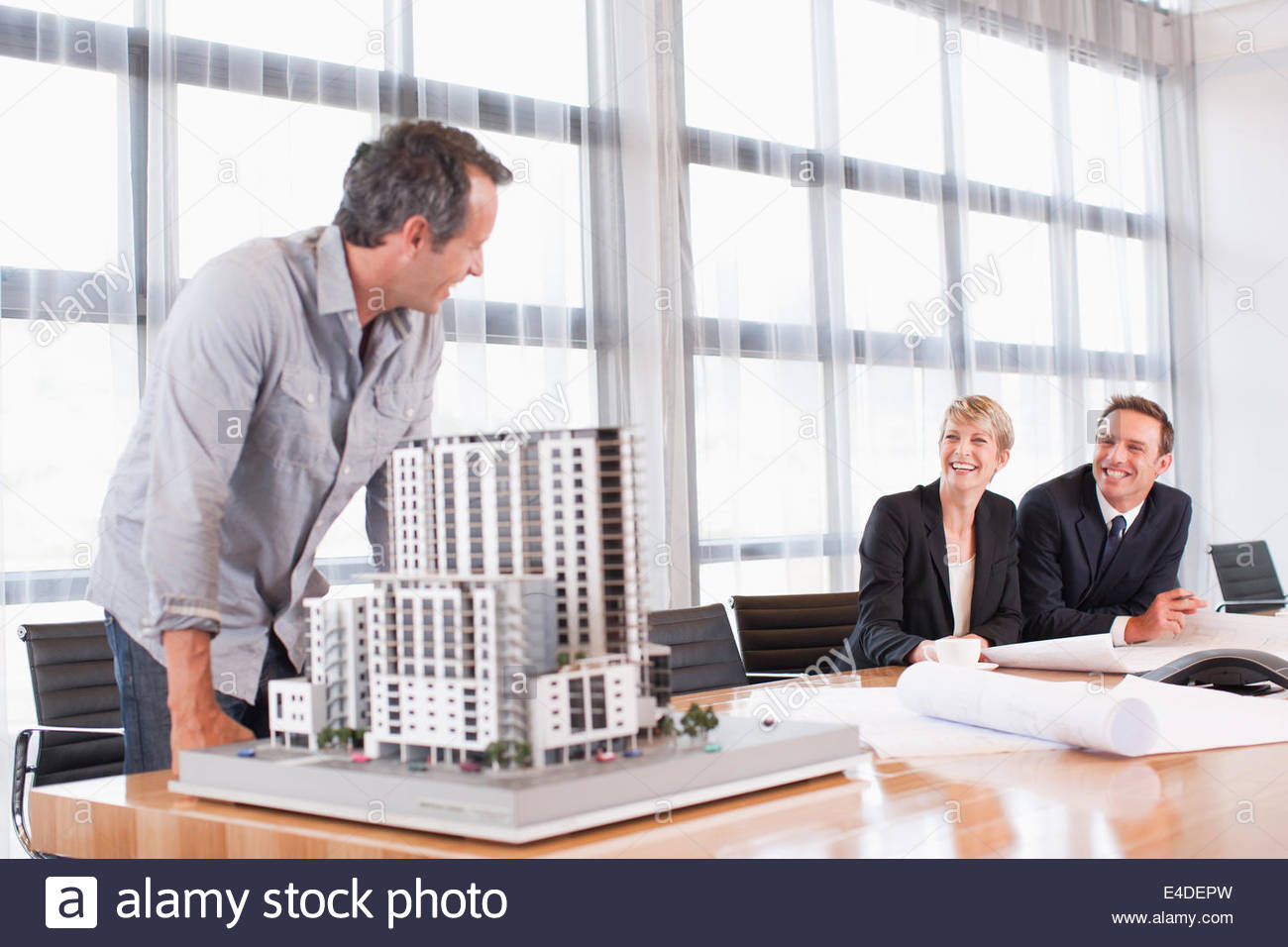 Architects in conference room with building model - Stock Image