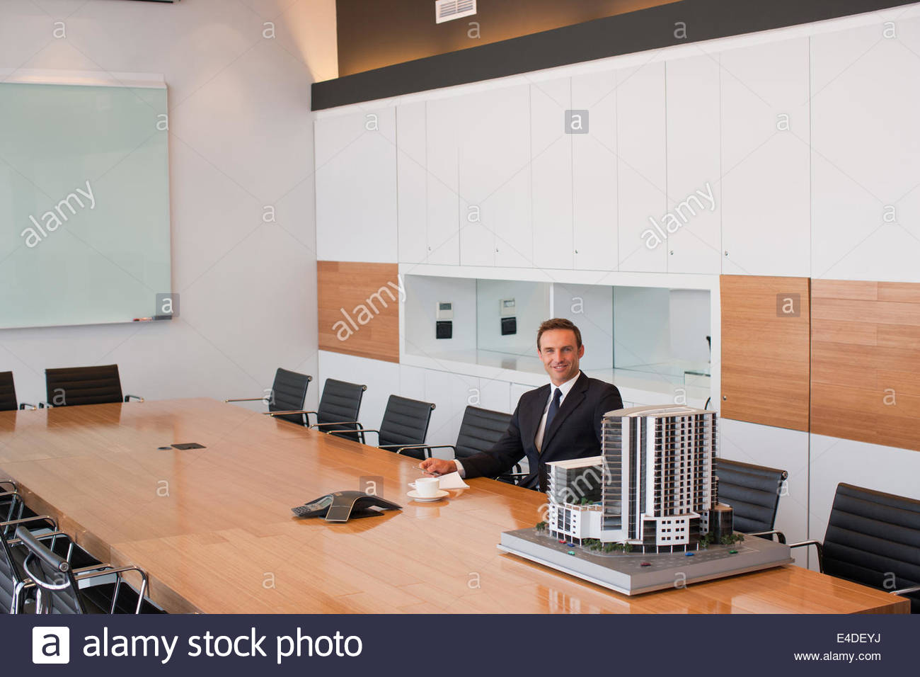 Businessman in conference room with building model Stock Photo