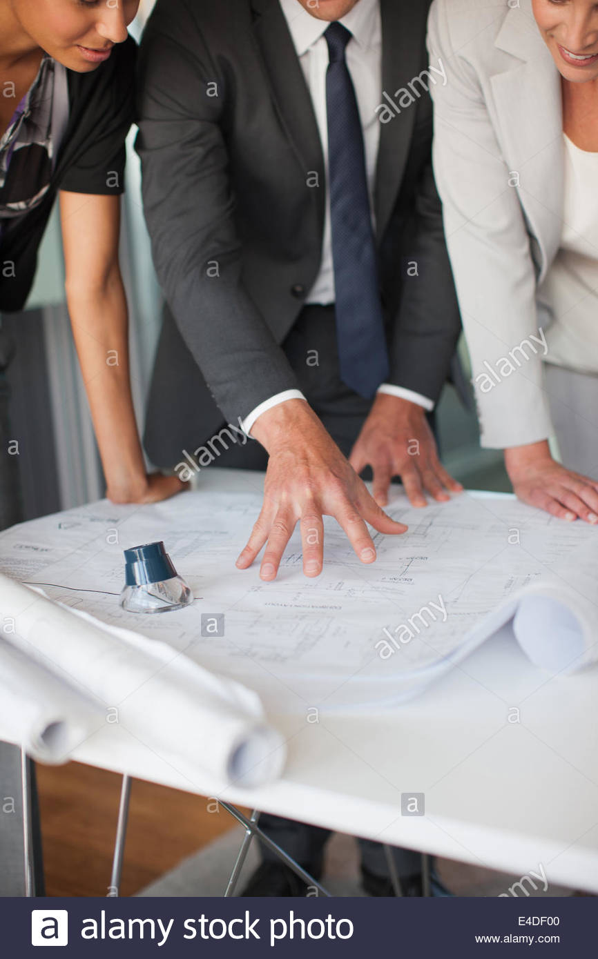 Architects looking at blueprints in office - Stock Image