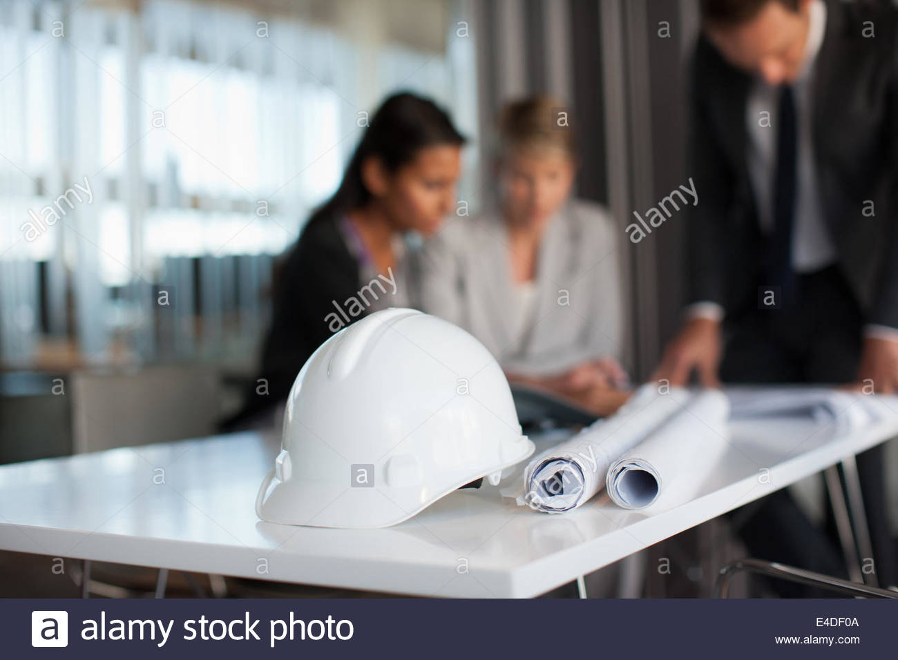 Business people reviewing blueprints in conference room - Stock Image