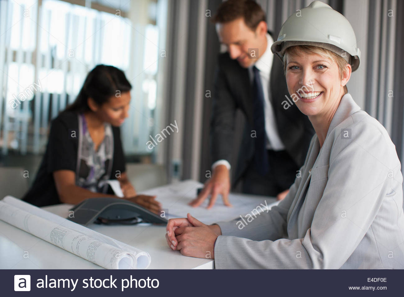 Businesswoman in conference room with blueprints - Stock Image