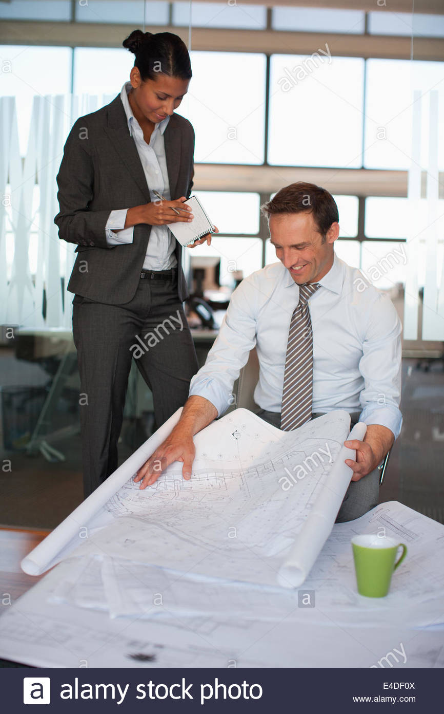 Business people reviewing blueprints together in office - Stock Image