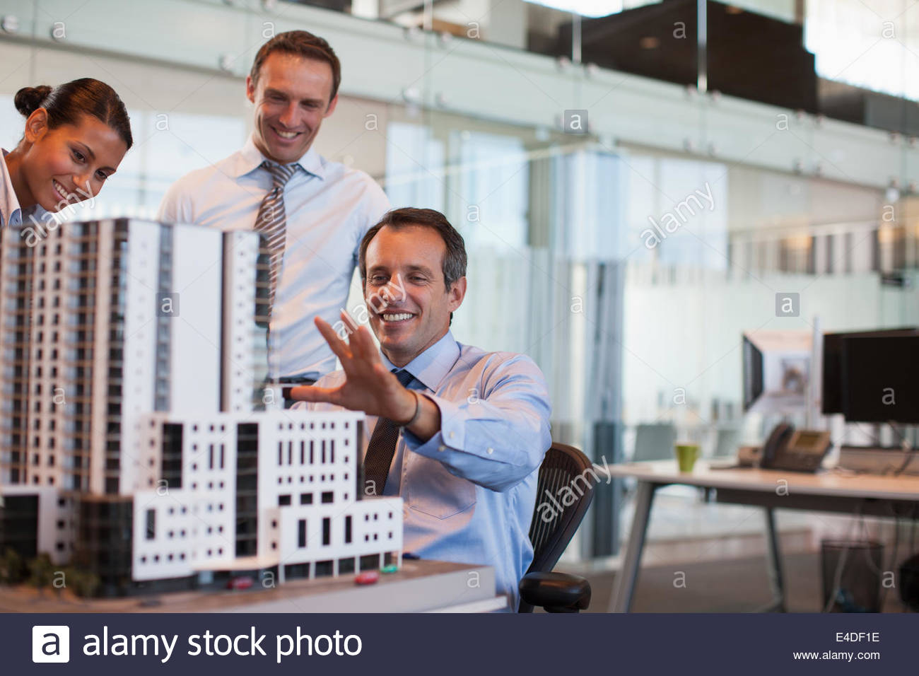 Business people looking at model building in office - Stock Image