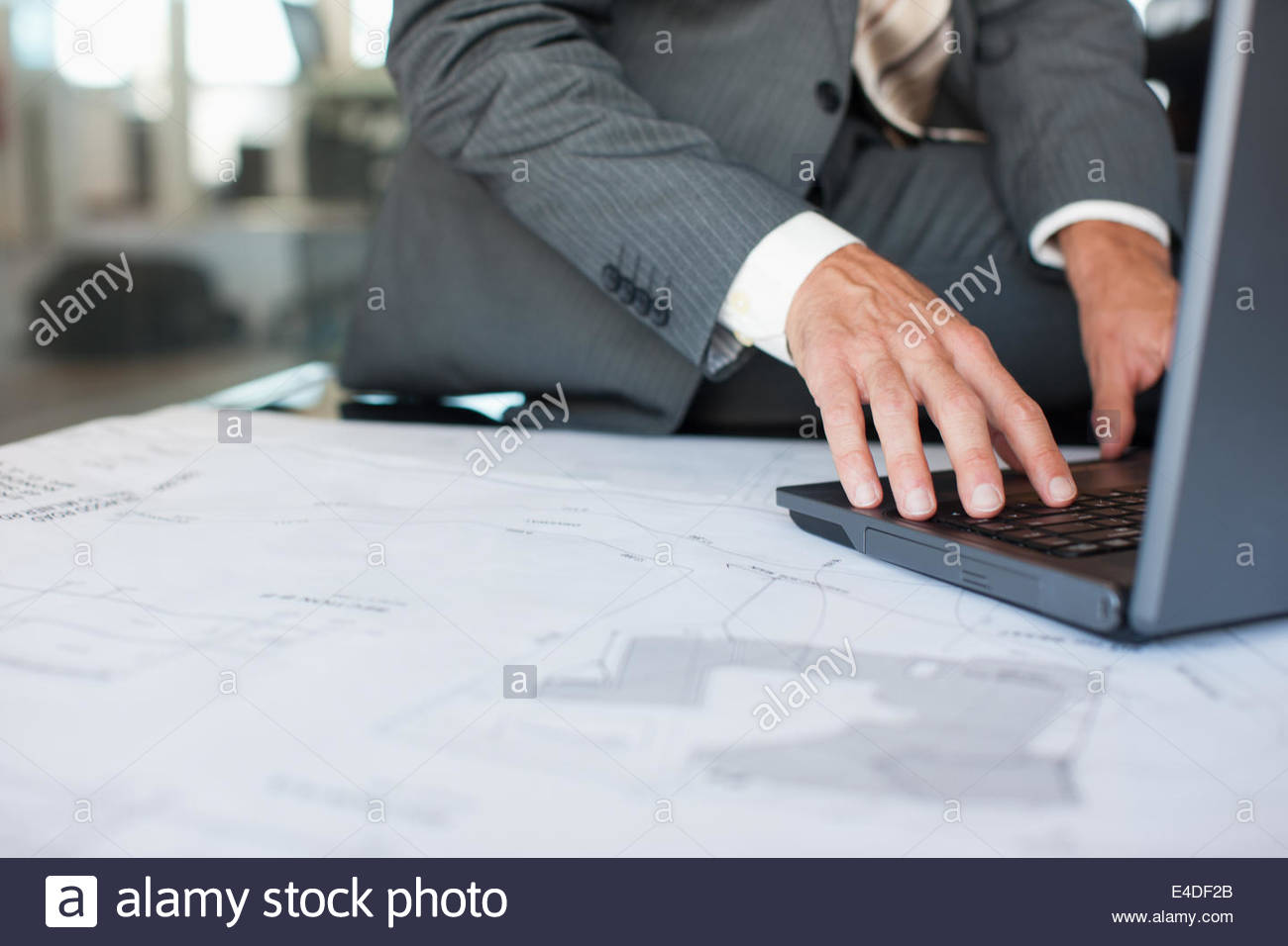 Businessman using laptop with blueprints in office - Stock Image