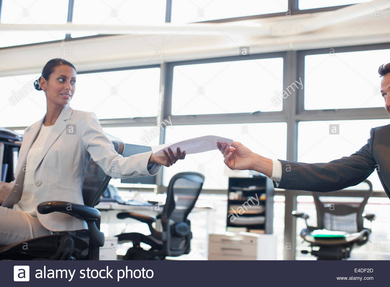 Businessman handing co-worker paperwork in office - Stock Image