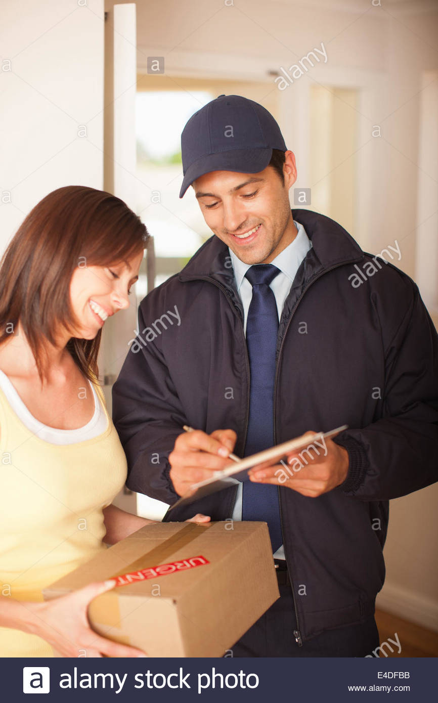 Woman signing box receipt for delivery man - Stock Image