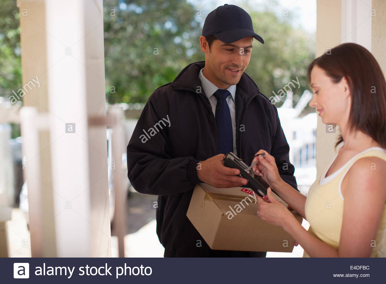 Woman signing for box from delivery man - Stock Image
