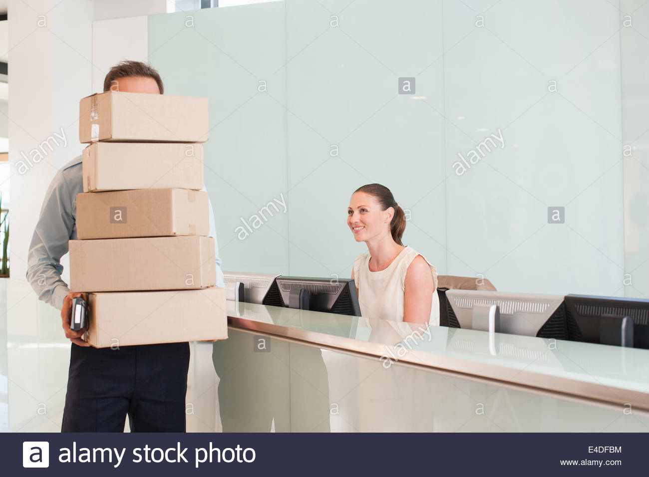 Delivery man holding stack of boxes in reception area - Stock Image