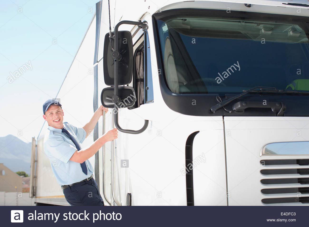 Truck driver standing on side of semi-truck - Stock Image