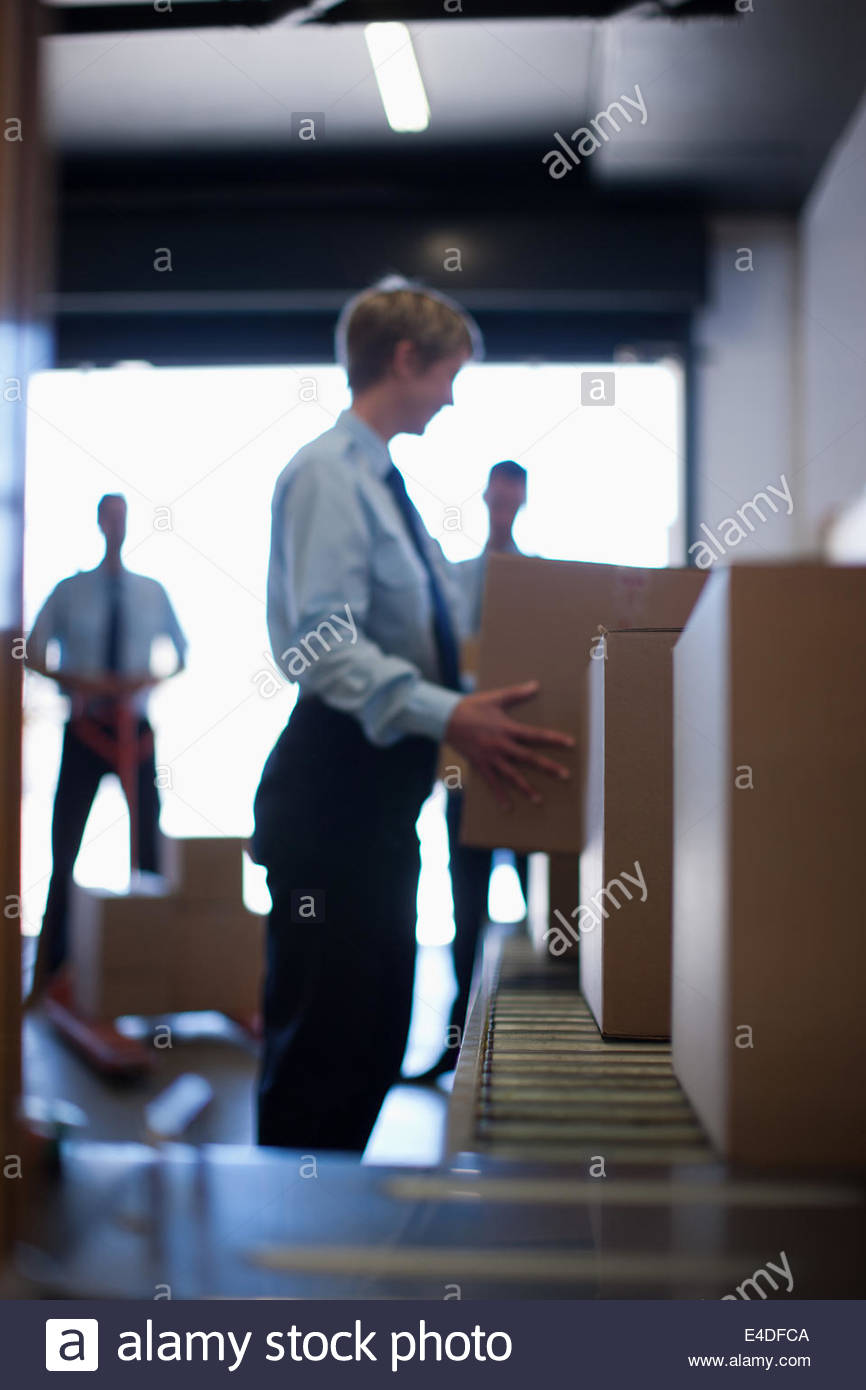 Workers taking boxes from conveyor belt in shipping area - Stock Image