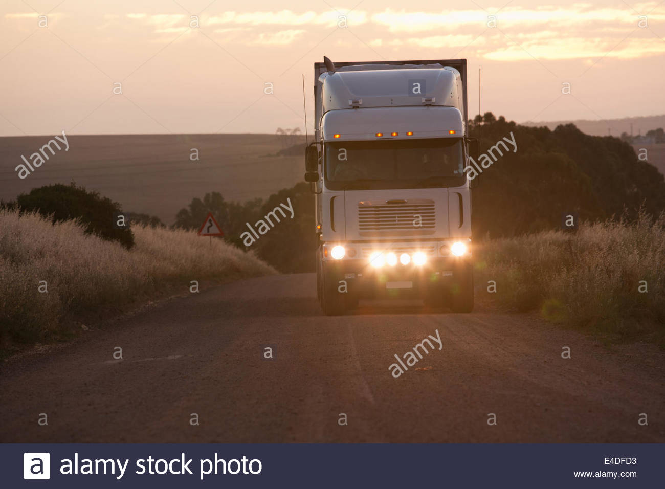 Semi-truck driving in dirt road - Stock Image
