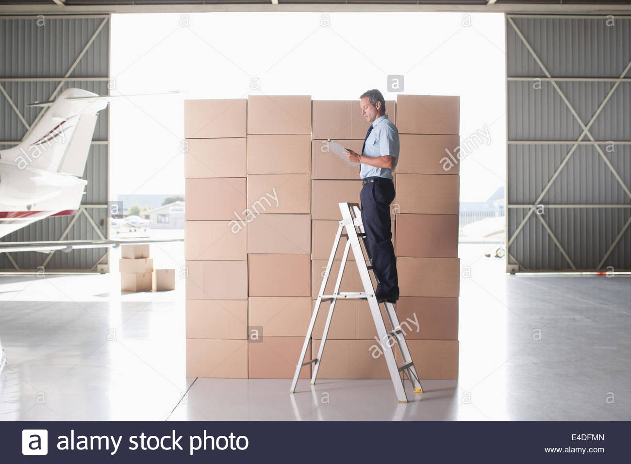 Worker stacking boxes in hangar Stock Photo