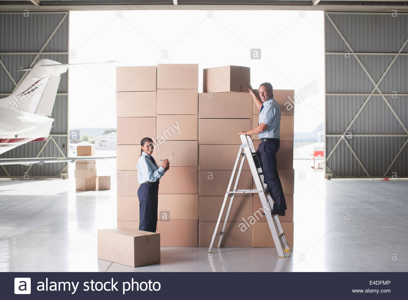 Workers stacking cardboard boxes in hangar - Stock Image