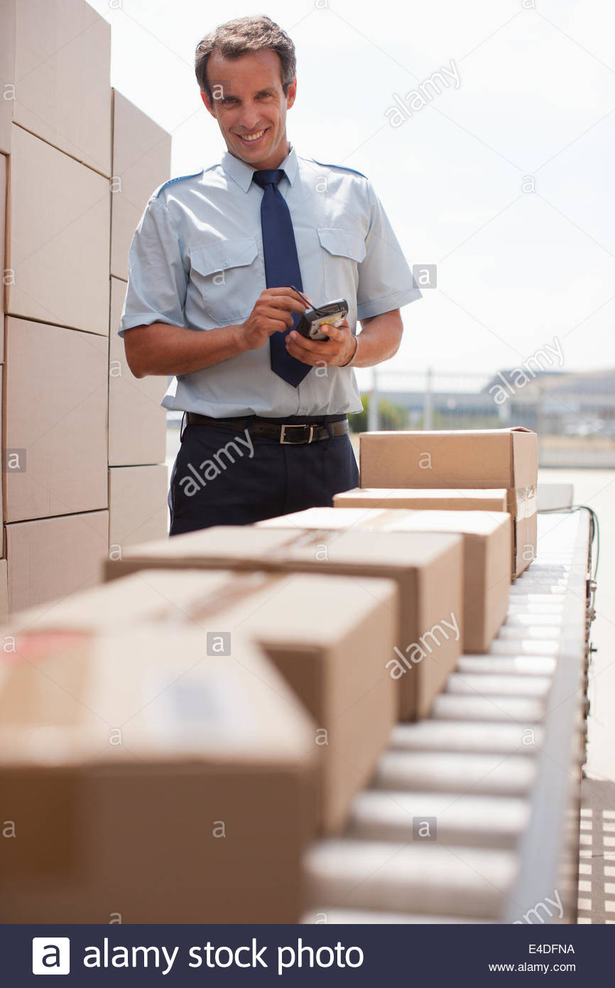 Worker standing near boxes on conveyor belt - Stock Image