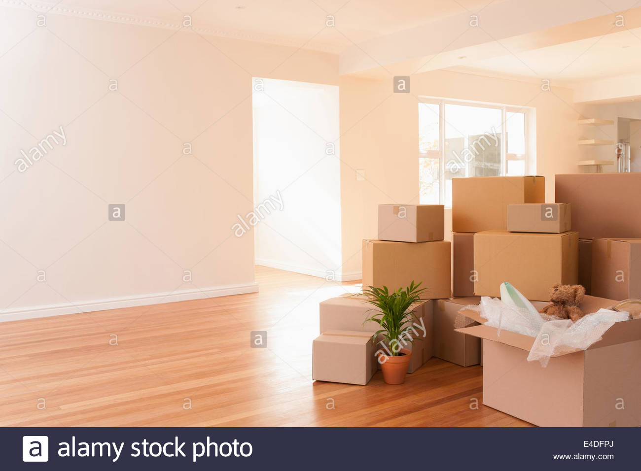 Boxes stacked on wooden floor of new house - Stock Image