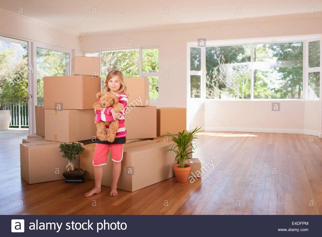 Girl hugging teddy bear in new house - Stock Image
